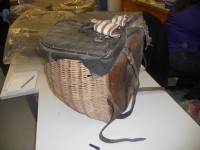 Side view of one of pair of panniers at Dumfries Museum, showing leather back