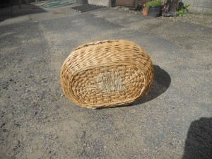 Base of shopping basket woven with split cane and repaired with string